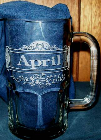Etched beer mug with decorative flowers and fine lines.