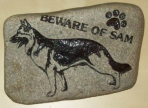 A sancarved rock depicting a dog graphic.